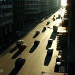 Cars on a city road at sunset.